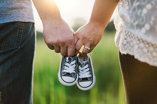 Couple holding hands and baby shoes