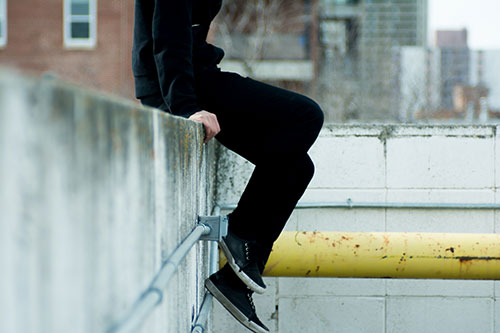 Teenager sitting on a ledge